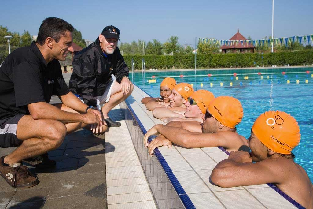 Image of coaches on poolside talking to 5 athletes in the water